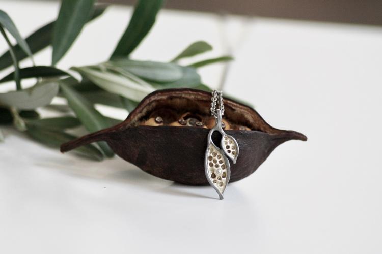 Ett långt bronshalsband på kedja med naturliga ihåligheter och frökapselns frukter. Smycket är format i vax och avgjutet från naturens skönhet.
