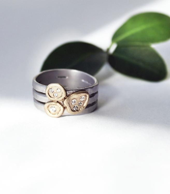 Dess band består av tre tunnare band som är sammanlänkade, vilket ger ett elegant uttryck. I mitten finner du kluster av ljuvligt glittrande safirer, mot en botten av guld.