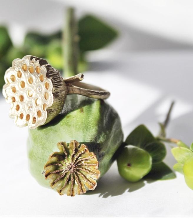 Lotus Ring är inspirerad av frökapseln av den blommade lotusblomman och är tillverkad i brons helt täckt i matt 14K guld, detaljerat med vita gnistrande safirer.