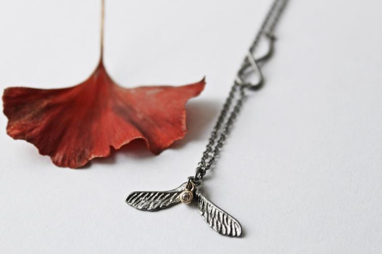 Dazzle Maple Nose Halsband från Lotta Jewellery är gjort i brons. Halsbandet är dekorerat med en vacker vit safir och detaljer i 14 k guld.