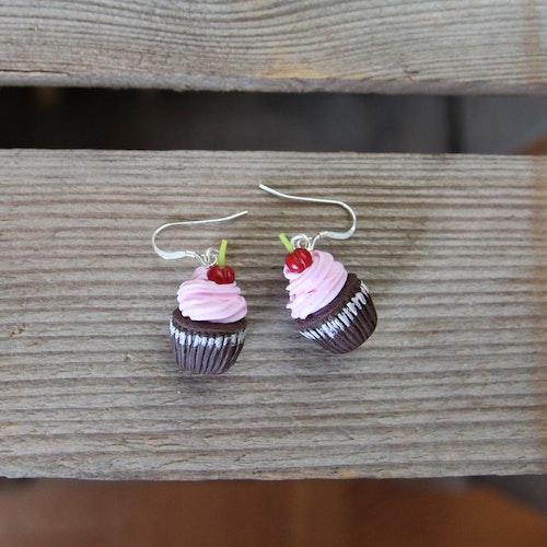 Örhängen, chokladcupcakes med rosa frosting och körsbär.