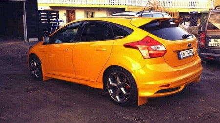 Orange bil med svarta stänkskydd