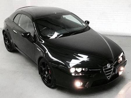 Svart Alfa Romeo med svarta fälgar och svarta stänklappar