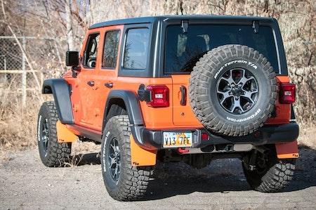 Jeep bakifrån med reservdäck och tillbehör som stänklappar i samma färg som bilens