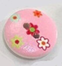 Rund träknapp rosa bakgrund och små blommor två hål