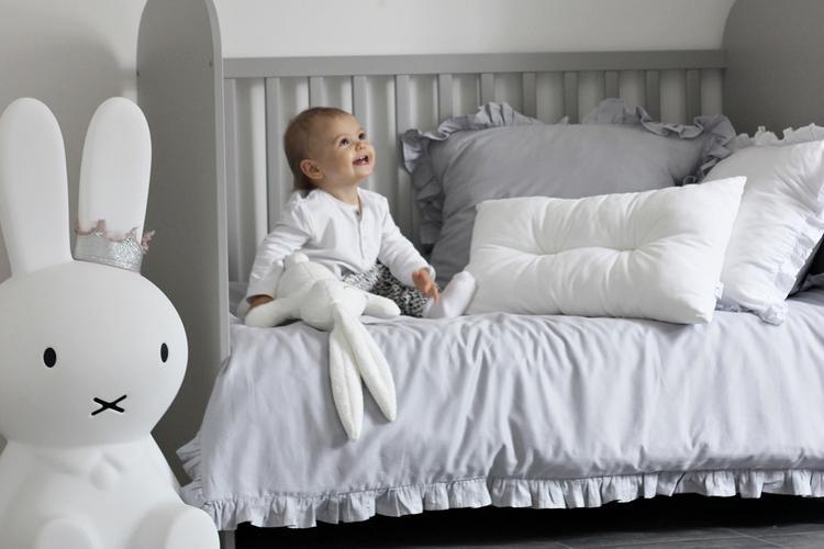 Grå bäddset spjälsäng med kudde och täcke med volang, Cotton and Sweets barn sitter på grå påsklakanset med volang