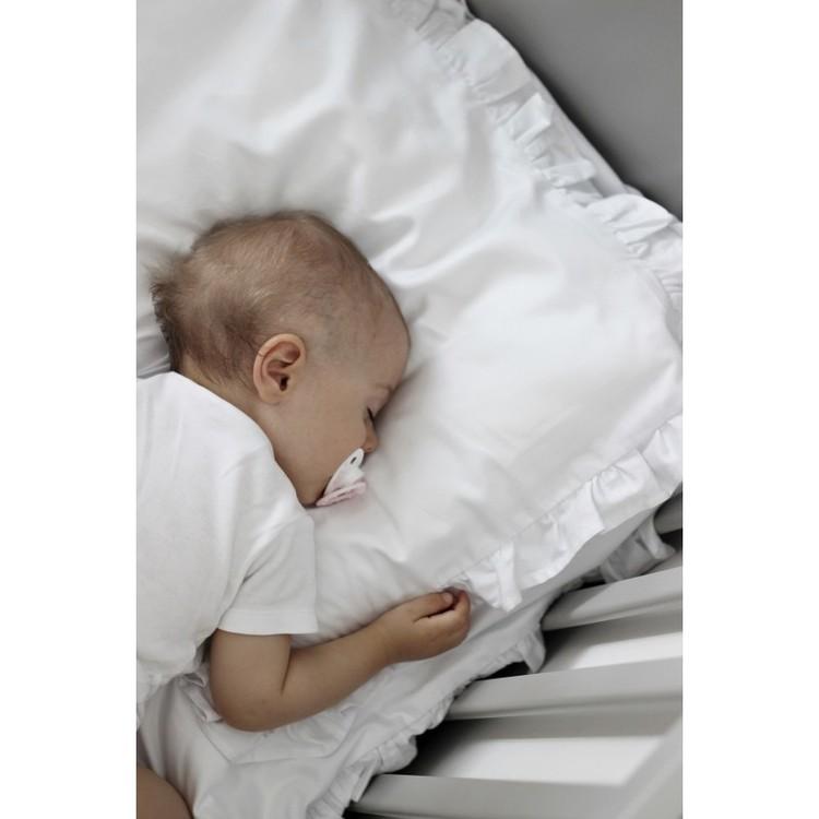 Vit bäddset spjälsäng med kudde och täcke med volang, Cotton and Sweets sovande barn på vit kudde med volang