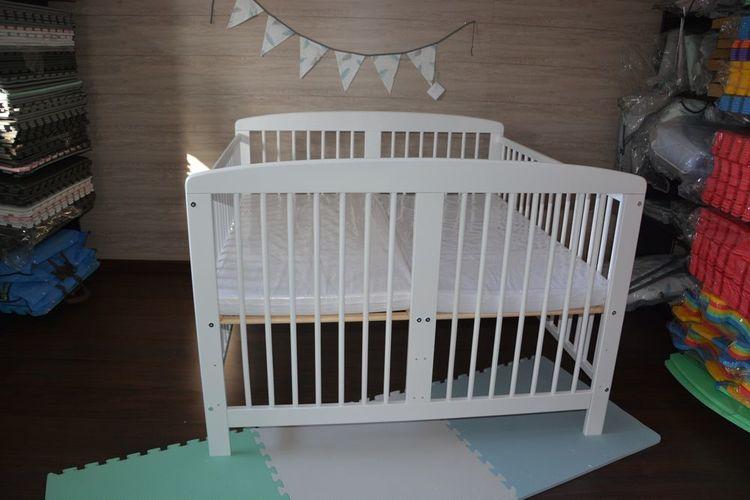 Vit spjälsäng för tvillingar med två madrasser