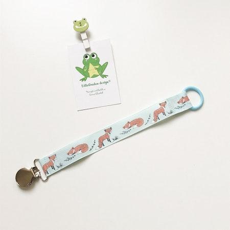 Napphållare med tecknade rävar - Metallclips Silver, silikonring Babyblå