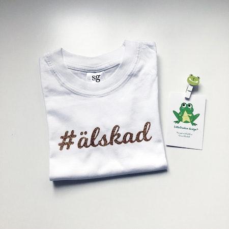 T-shirt i vitt med #älskad i guldglitter