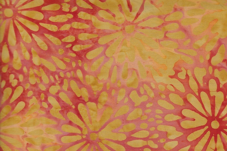 Rödorangeflammigt tyg med senapsgula blomstermotiv