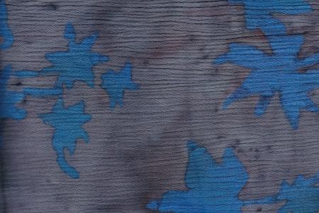 Grått och med blåa stiliserade palmer och blommor. Kräppad viskos.