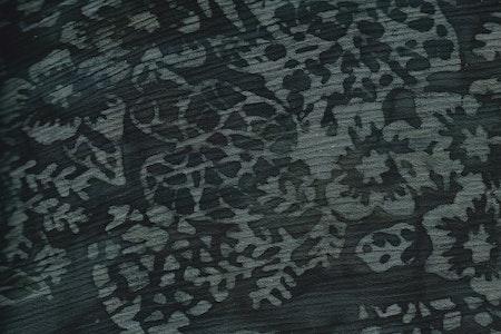 Svartflammigt med grågrönt fantasimönster med blommor och blad.