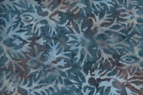 Blå-brunflammigt trikåtyg med ljusblå växttryck. 100% bomull