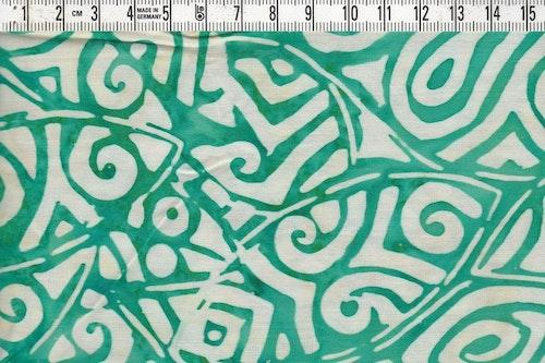 Batiktyg med grönt motiv och vit bakgrund. Bomull ca 110 cm