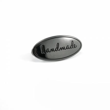 """Metallmärke """"handmade"""" att pryda egengjord väska tex. Gunmetal. Från Emmaline Bags"""
