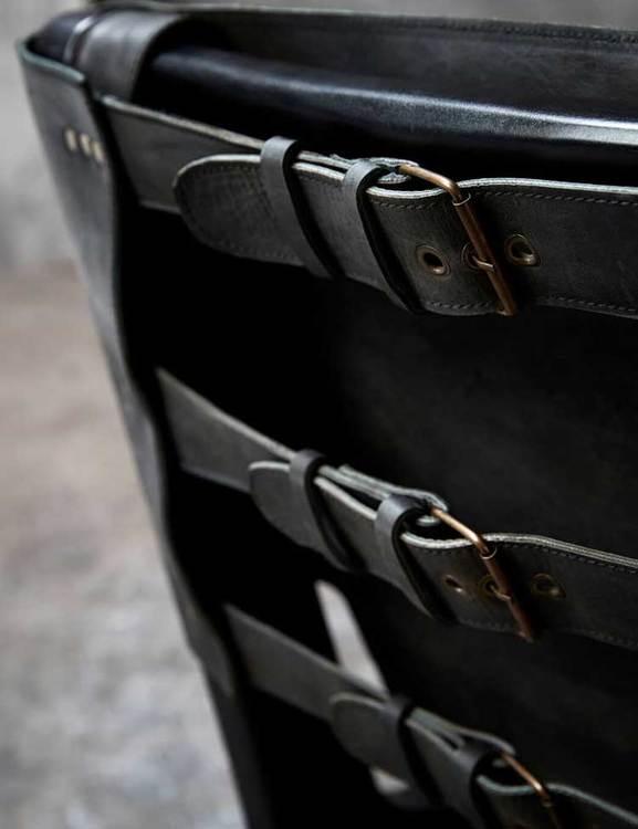 Loungefåtölj med en rygg dekorerad med bältesspännen