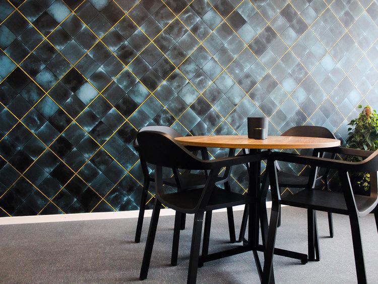 Tapet i ett café med akvarellmönstrade kakelplattor inramade av guldlister.