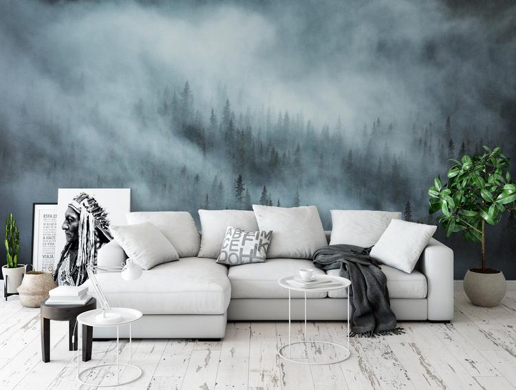 Tapet i vardagsrum med soffa framför fototapet av dimmig skog.