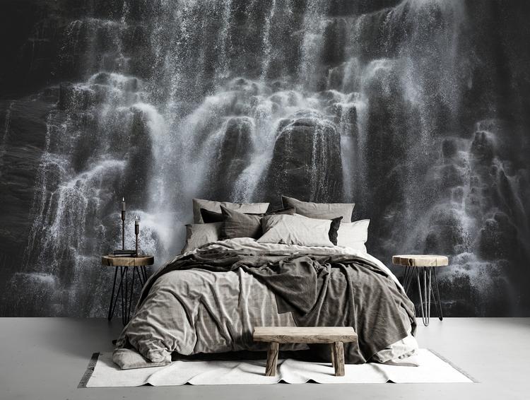 Fototapet föreställande ett vattenfall med obäddad säng framför.