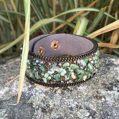 Armband i grå konstmocka med skimrande gröna stenar