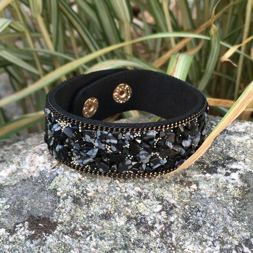 Armband i svart konstmocka med skimrande stenar