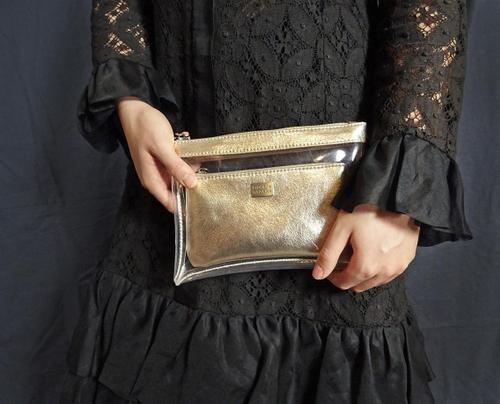 Platt, genomskinlig necessär i plast från Pipol´s Bazaar med en guldig innerväska i konstgjort skinn. Använd den till smink, eller som en extra väska i en stor större väska. Den kan även användas som