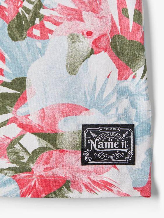 Mjuk T-shirt med ett heltäckande sommarinspirerat tryck från Name it, tillverkad i ekologisk bomull. T-shirten har rund hals och ett litet uppvik i ärmsluten. Material: 95% Ekologisk Bomull och 5% Ela