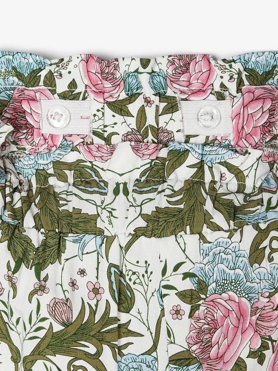 Tunn blommig paperbag byxa från Name it med justerbar midja, fickor i sidorna och resår i bensluten. Material: 100% Viskos  Färg: Vit