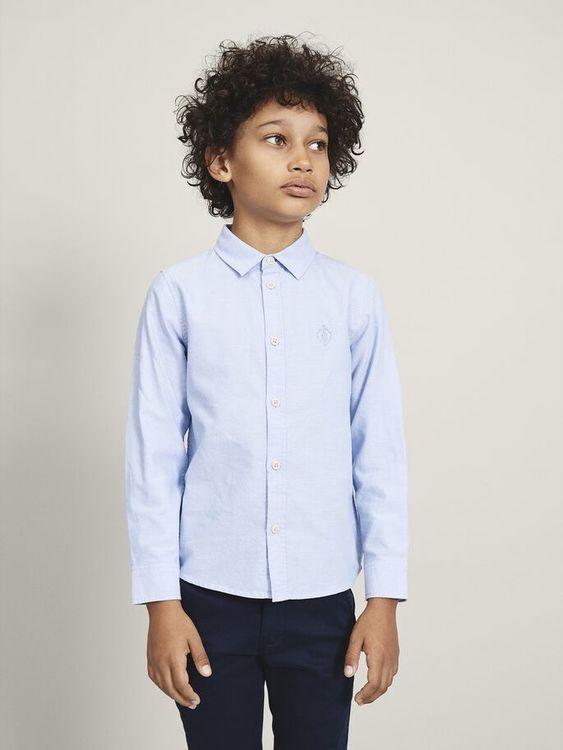 Snygg långärmad oxfordskjorta från Name it med klassisk krage, knappknäppning fram och en broderad detalj på bröstet i samma färg. Material: 100% Bomull  Färg: Ljusblå