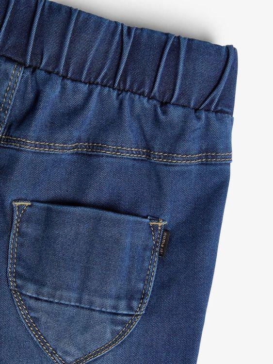 Mjuka och mycket stretchiga jeans i regular fit till flickor från Name it med justerbar midja och en smidig tryckknappsstängning. Jeansen har en snygg veckad detalj framtill samt muddar i bensluten. M