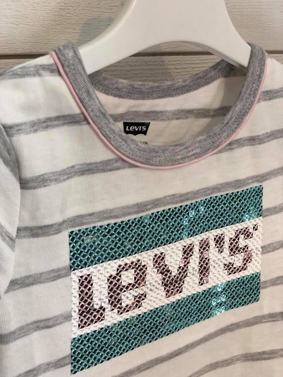 Söt randig T-shirt från Levi´s med rund hals som pryds av grått och rosa kantband,  paljetter fram med texten Levi´s samt en holkärm. Material: 60% Bomull och 40% Polyester   Färg: Vit