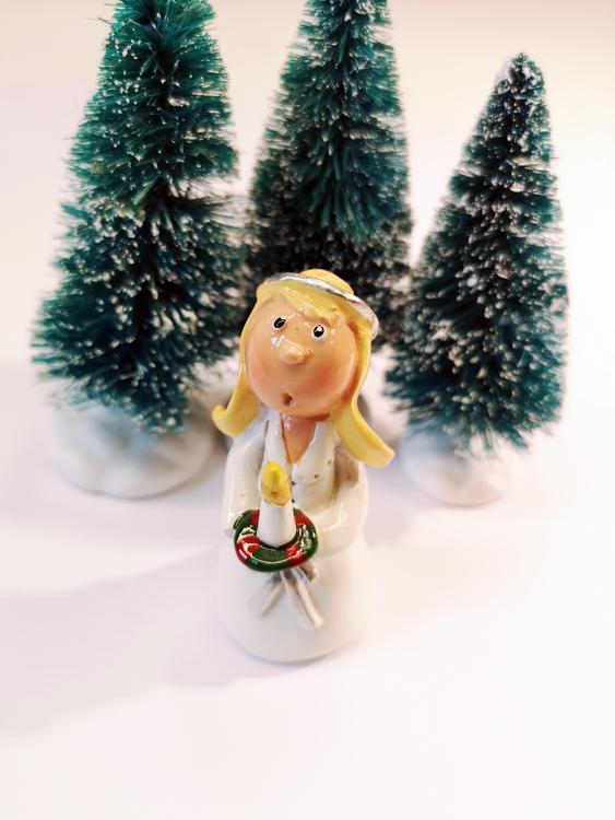 Figur föreställande luciatärna med blont hår och ljus i handen.