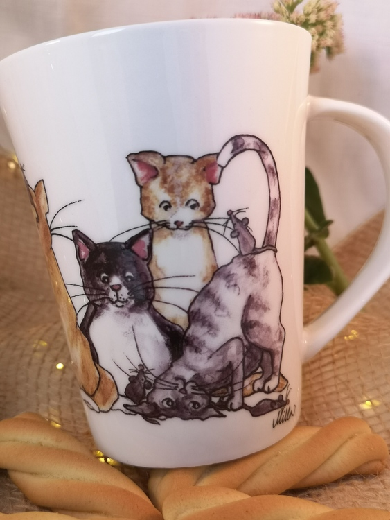 Mugg med kattmotiv. Tre katter i olika färger tittar på möss på denna sida av muggen.