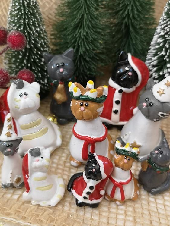 Kattfigurer i tomtedräkt, lucialinne och stjärngosseskjorta samt med bjällra.