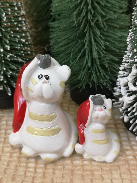 Julfigurer föreställande två vita katter i tomteluva.