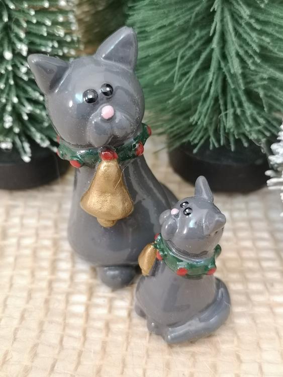 Gråa katter i två storlekar med bjällra runt halsen.