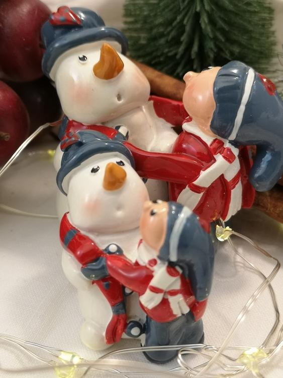 Figur föreställande snögubbe som får halsduken knuten av ett barn.