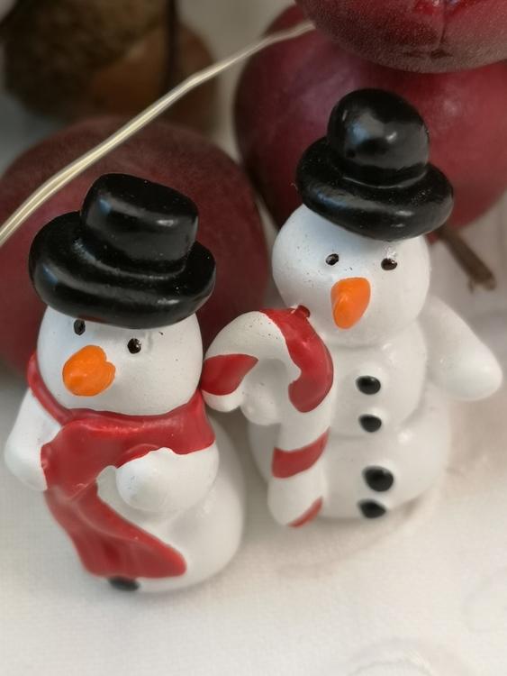 Små snögubbar med hatt och halsduk respektive hatt och polkagris.