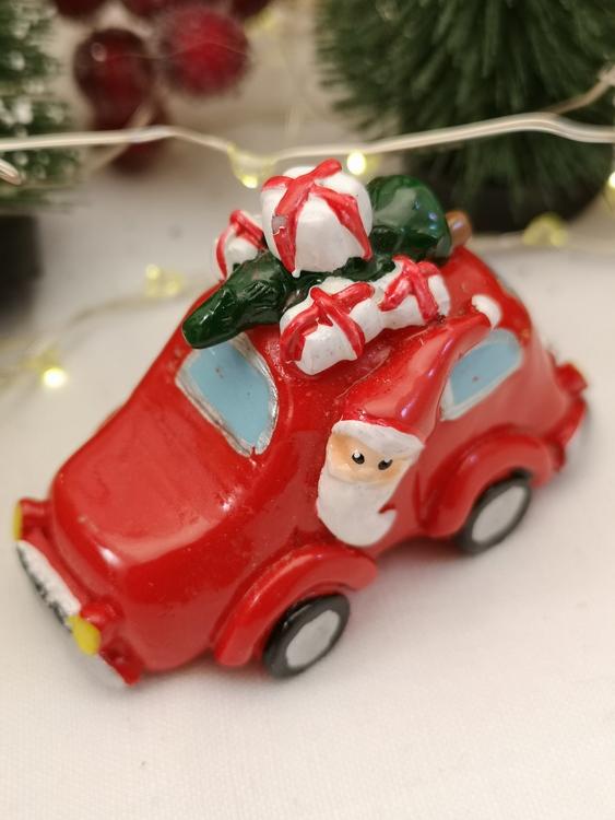 liten röd bil med jultomte