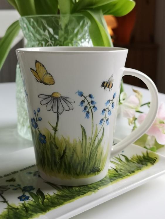 Motiv av fjärilar, bin, gräs och blommor på mugg.