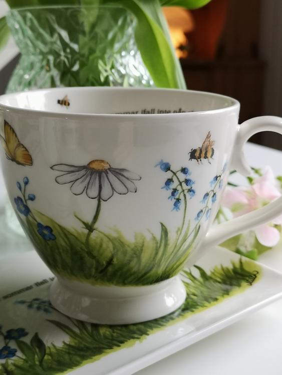 Tekopp med naturmotiv där det syns blommor, fjärilar och bin.