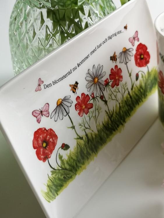 Assiett med rektangulär form med motiv av vita och röda blommor samt fjärilar och bin. Även text på assietten.
