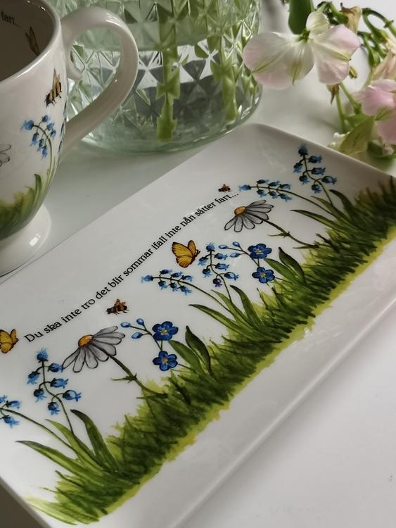 Vita och blåa blommor på assiett med text.