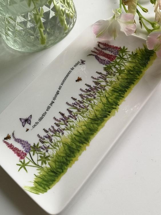 Rektangulär assiett med röda och lila blommor samt fjärilar och bin.