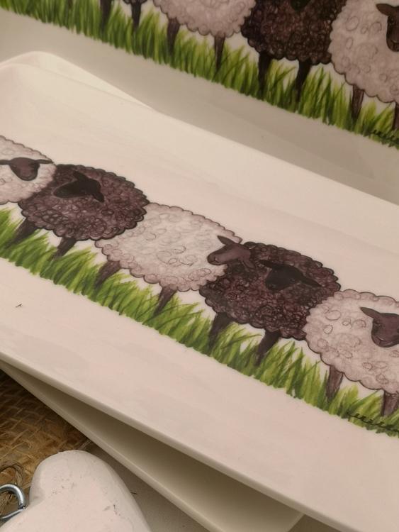 Rektangulär assiett i porslin med motiv av fyra får som står i rad på gräs.