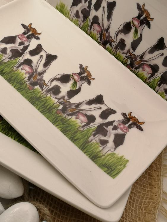 Assietter gjorda i porslin med kor på rad stående på fält. Några tittar fram och andra syns bakifrån.