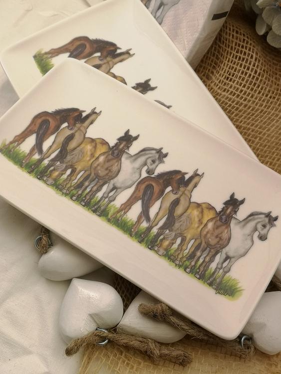 Hästassiett i porslin med rektangulär form med hästar på rad. Hästarna har olika färger och står på gräs.