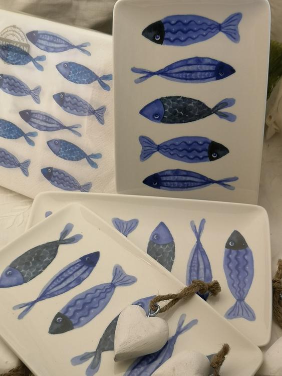 Assietter med blåa fiskar som motiv. Varannan har huvudet uppåt respektive nedåt.