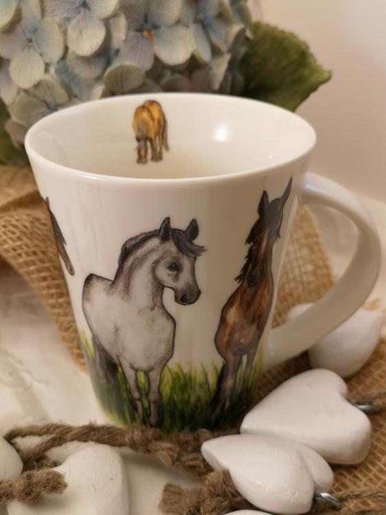 Motiv med hästar och högt gräs på mugg. Ytterligare mindre häst på insidan av koppen.
